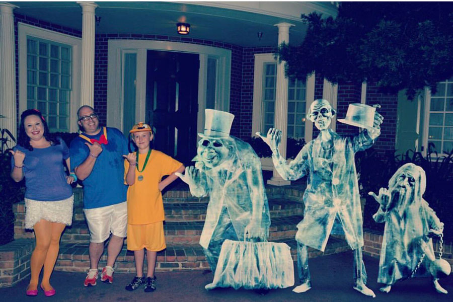 Family wearing Daisy, Donald and Pluto costumes take a Disney PhotoPass MagicShot with the Hitchhiking Ghosts